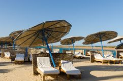 Sunbeds on the beach. Sunbeds with umbrellas on the beach with nobody around Royalty Free Stock Photos