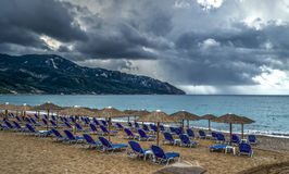 Sunbeds on the beach, no one around cause of the approaching storm. 