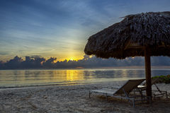 Sunbeds on the beach at sunrise. Sunbeds under a thatched shade on a Caribbean beach at sunrise Stock Photo