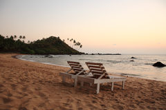 Sunbeds on the beach at sunset Stock Photography
