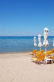Sunbeds on a beach and turquoise water Stock Image