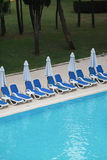 Sunbeds, beach umbrellas, pool, grass, trees Royalty Free Stock Photos