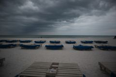 Sunbeds with blue towels on a sandy beach in stormy weather. gray thunder clouds.  royalty free stock image
