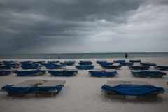 Sunbeds with blue towels on a sandy beach in stormy weather. gray thunder clouds.  stock photo