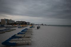 Sunbeds with blue towels on a sandy beach in stormy weather. gray thunder clouds.  stock photography