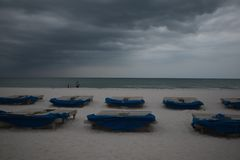 Sunbeds with blue towels on a sandy beach in stormy weather. gray thunder clouds.  royalty free stock photos