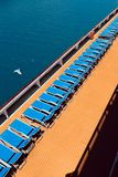 Sunbeds on boat. Comfortable blue lounger on wooden floor on the deck of a cruise ship. Vertical photography stock photo