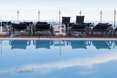 Sunbeds cerca de la piscina Fotografía de archivo libre de regalías