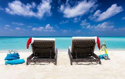 Sunbeds with Christmas hats on a tropical beach stock image