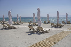 Sunbeds with closed umbrellas on a beach with sand. Royalty Free Stock Photos