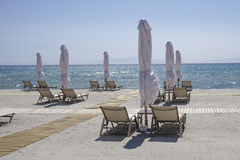 Sunbeds with closed umbrellas on a beach with sand. Stock Images