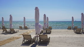 Sunbeds with closed umbrellas on a beach with sand. stock video