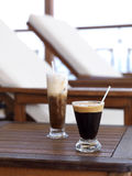 Sunbeds and coffee. Cappuccinos served at a balcony with two sunbeds royalty free stock image