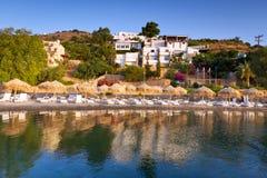 Sunbeds con los parasoles en la bahía de Mirabello Foto de archivo