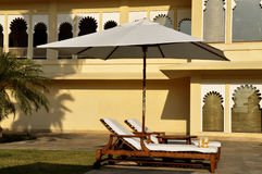 Sunbeds contro architettura medioevale in Udaipur fotografie stock