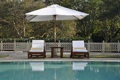 Sunbeds door een zwembad in het midden van groen Stock Foto