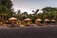 Sunbeds e os restaurantes em um balinese encalham na noite imagem de stock