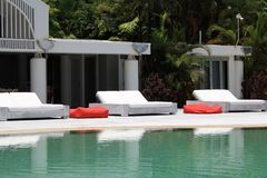 Sunbeds en la piscina Imagen de archivo