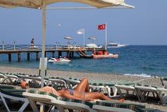 Sunbeds en paraplu's in strandtoevlucht, meisje sunbath op lanterfanter Stock Foto's