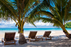 Sunbeds on exotic tropical palm beach Stock Images