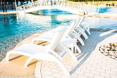 Sunbeds fuera de la piscina imagen de archivo libre de regalías