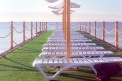 Sunbeds on the grass by the sea. With yellow fence royalty free stock photos