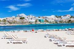Sunbeds i piękny miasto widok na pięknej plaży w Ibiza, Hiszpania Obrazy Royalty Free