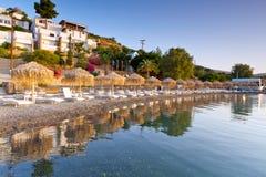 Sunbeds med ett slags solskydd på den Mirabello fjärden på Crete Arkivbilder