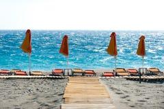 Sunbeds med paraplyer på stranden Fotografering för Bildbyråer