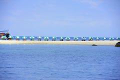 Sunbeds med paraplyer på stranden på blå bakgrund Royaltyfria Bilder
