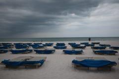 Sunbeds met blauwe handdoeken op een zandig strand in stormachtig weer grijze donderwolken stock foto