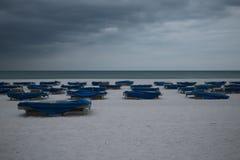 Sunbeds met blauwe handdoeken op een zandig strand in stormachtig weer grijze donderwolken royalty-vrije stock foto