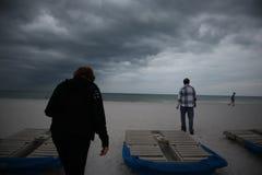 Sunbeds met blauwe handdoeken op een zandig strand in stormachtig weer grijze donderwolken stock fotografie