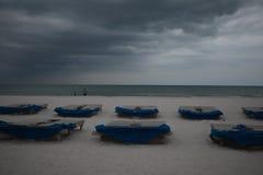 Sunbeds met blauwe handdoeken op een zandig strand in stormachtig weer grijze donderwolken royalty-vrije stock foto's