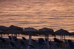Sunbeds mit Regenschirmen auf dem Strand morgens, Momente Befo Lizenzfreies Stockbild