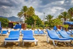 Sunbeds na piasku na tropikalnej miejscowości nadmorskiej w złej pogodzie z chmurnym niebem Drzewka palmowe i bryczka hole na pla Zdjęcia Royalty Free