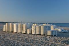Sunbeds na praia empilhada, apronta-se para ser posto sobre a praia ao en Imagem de Stock Royalty Free