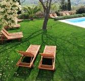 Sunbeds naast een zwembad in tuin Royalty-vrije Stock Afbeeldingen