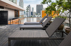 Sunbeds nahe bei einem Swimmingpool auf Dachspitze. Stockbild