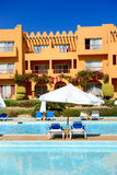 Sunbeds near swimming pool at luxury hotel Royalty Free Stock Photography