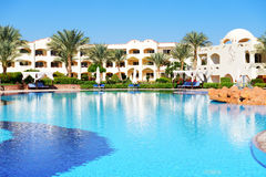 Sunbeds near swimming pool at luxury hotel Stock Photography