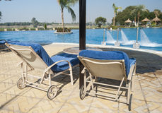 Sunbeds next to tropical pool Stock Photography