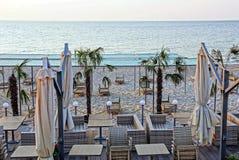 Sunbeds och möblemang med paraplyer på stranden med palmträd i sanden mot himlen och havet arkivbilder