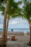 Sunbeds och palmträd på stranden på havsbakgrund med skepp Pandan Panay, Filippinerna Royaltyfri Foto