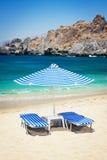 Sunbeds och paraply på stranden Royaltyfri Bild
