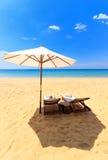 Sunbeds och paraply på stranden Arkivfoto