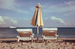 Sunbeds och paraply på stranden Arkivbild