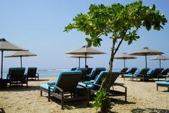 Sunbeds och paraplyer på stranden vid havet Royaltyfri Foto