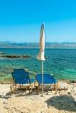 Sunbeds och paraplyer (slags solskydd) på den Kassiopi stranden, Korfu ö, Grekland Arkivfoto