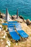 Sunbeds och paraplyer (slags solskydd) på stranden i den Korfu ön, Grekland Arkivbilder